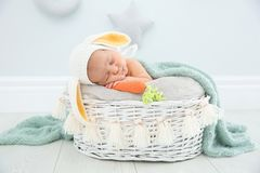 Adorable newborn child wearing bunny ears hat in baby nest. Indoors royalty free stock photography