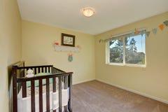 Adorable nursery room. Pastel yellow interior paint and carpet floor stock photos