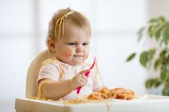 Adorable one-year baby try to catch a pasta Stock Photos