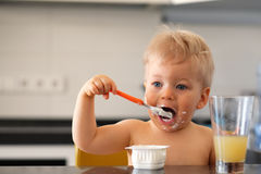 Adorable one year old baby boy eating yoghurt with spoon Royalty Free Stock Image