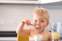 Adorable one year old baby boy eating yoghurt with spoon Stock Images