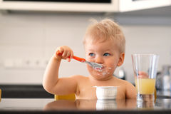 Adorable one year old baby boy eating yoghurt with spoon Stock Photos