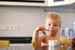 Adorable one year old baby boy eating yoghurt with spoon Royalty Free Stock Images