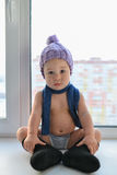 Adorable one year old baby boy lonely sitting on the windowsill weared in winter hat, shoes and scarf, indoors. royalty free stock photography