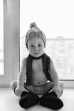 Adorable one year old baby boy lonely sitting on the windowsill weared in winter hat, shoes and scarf, indoors. stock photography