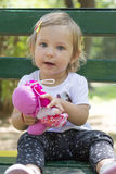 Adorable one year old baby girl sitting on a bench with a doll i Royalty Free Stock Photo