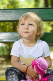 Adorable one year old baby girl sitting on a bench with a doll i Royalty Free Stock Images