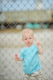 Adorable one year old boy. Behind a gate Royalty Free Stock Photos