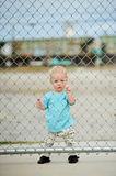 Adorable one year old boy. Behind a gate Stock Photo