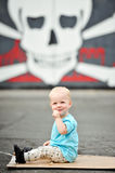 Adorable one year old boy. Eating a lollipop in front of a skull and crossbones painting Stock Photo