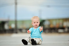 Adorable one year old boy train tracks. Adorable one year old boy sitting in front of a train Royalty Free Stock Image