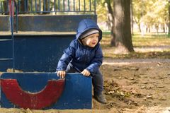 Adorable one year toddler playing in the autumn park on the children playground royalty free stock photography