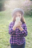 Adorable pre-teen tweenie brunette kid girl with her smartphone in the spring park. Dressed in shirt and blue hat Royalty Free Stock Image