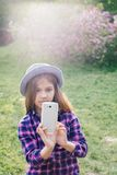 Adorable pre-teen tweenie brunette kid girl with her smartphone in the spring park. Dressed in shirt and blue hat Royalty Free Stock Photos