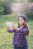 Adorable pre-teen tweenie brunette kid girl with her smartphone in the spring park. Dressed in shirt and blue hat Stock Photo
