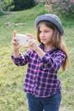 Adorable pre-teen tweenie brunette kid girl with her smartphone in the spring park. Dressed in shirt and blue hat Stock Images