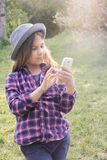 Adorable pre-teen tweenie brunette kid girl with her smartphone in the spring park. Dressed in shirt and blue hat Royalty Free Stock Photography