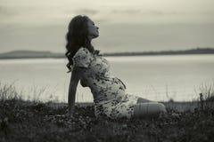 Adorable pregnant woman lying on the grass Stock Photos