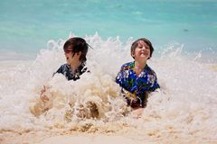 Adorable preschool children, boys, having fun on ocean beach. Excited children playing with waves, swimming, splashing happily. Enjoying family vacation in stock photos