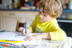 Adorable preschool kid boy painting with colorful pencils police car Stock Photos