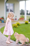Adorable preschooler girl and a cat outdoors Royalty Free Stock Photography