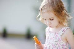 Adorable preschooler girl eating carrot Royalty Free Stock Images