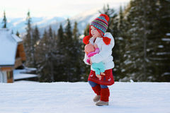 Adorable preschooler girl enjoys winter at ski resort Stock Photo