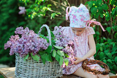 Adorable preschooler girl in pink plaid dress making lilac wreath in spring sunny garden Stock Photo