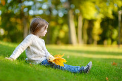 Adorable preschooler girl portrait on autumn day. Adorable preschooler girl sitting on a green grass and holding yellow maple leaves on beautiful autumn day Royalty Free Stock Images