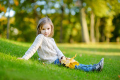 Adorable preschooler girl portrait on autumn day. Adorable preschooler girl sitting on a green grass and holding yellow mapple leaves on beautiful autumn day Stock Photo