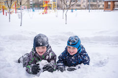 Adorable preschooler in winter wear sit amoung snow and play wit Stock Photo