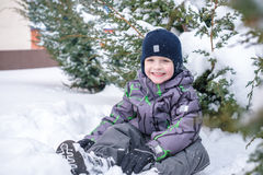 Adorable preschooler in winter wear sit amoung snow and play wit Royalty Free Stock Image