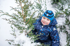 Adorable preschooler in winter wear sit amoung snow and play wit Royalty Free Stock Photos