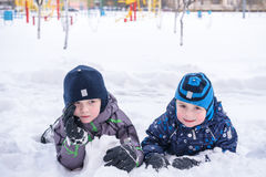 Adorable preschooler in winter wear sit amoung snow and play wit Stock Images