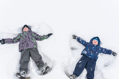 Adorable preschooler in winter wear sit amoung snow and play wit Royalty Free Stock Photography