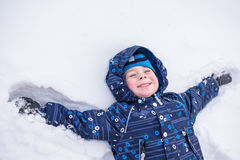 Adorable preschooler in winter wear sit amoung snow and play wit Stock Photos