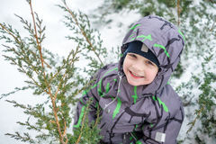 Adorable preschooler in winter wear sit amoung snow and play wit Royalty Free Stock Photo
