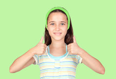 Adorable preteen girl accepting with the tumbs. On green background Stock Photo