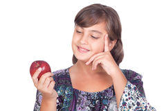 Adorable preteen girl with a apple thinking Stock Images