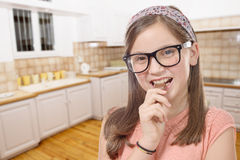 Adorable preteen girl with glasses eats chocolate, kitchen backg Royalty Free Stock Photo