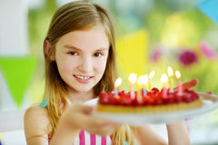 Adorable preteen girl having birthday party at home, blowing candles on birthday cake. Kids birthday party with colorful decorations, gifts and banners Royalty Free Stock Photography