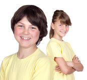 Adorable preteen girl and little boy in yellow. Isolated on white background Stock Photos