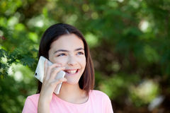 Adorable preteen girl with mobile. With plants of background Stock Images