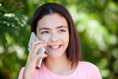 Adorable preteen girl with mobile. With plants of background Stock Photo