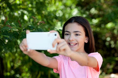 Adorable preteen girl with mobile. With plants of background Royalty Free Stock Image
