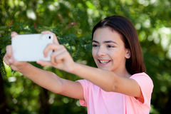 Adorable preteen girl with mobile. With plants of background Stock Image