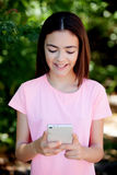 Adorable preteen girl with mobile. With plants of background Royalty Free Stock Photos