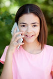 Adorable preteen girl with mobile. With plants of background Royalty Free Stock Images