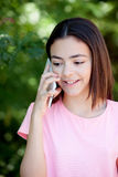 Adorable preteen girl with mobile. With plants of background Stock Photography