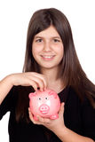 Adorable preteen girl with a piggy-bank. Isolated on white background Stock Images